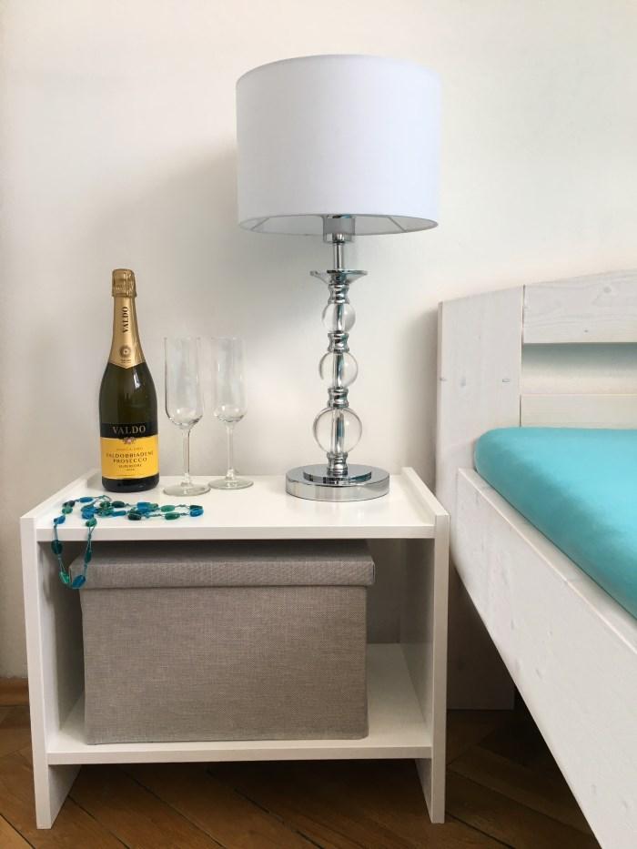 Der kleine Tisch fertig lackiert neben dem Bett. Darauf steht eine Tischleuchte und eine Flasche Sekt mit zwei Gläsern.