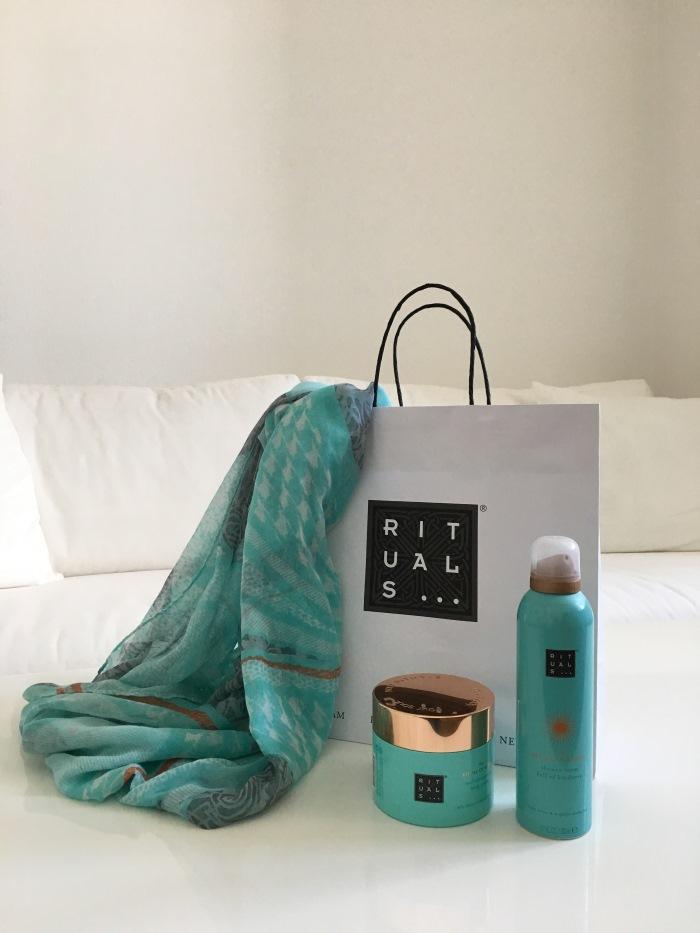 Rituals Dusche und Bodycreme neben mit einem gleichfarbigem Tuch und der Einkaufstüte