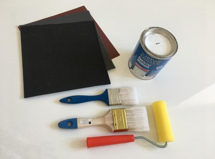 Die Materialien zur Gestaltung eines selbstgestalteten kleinen Tisches: Pinsel, Lack, Schleifpapier
