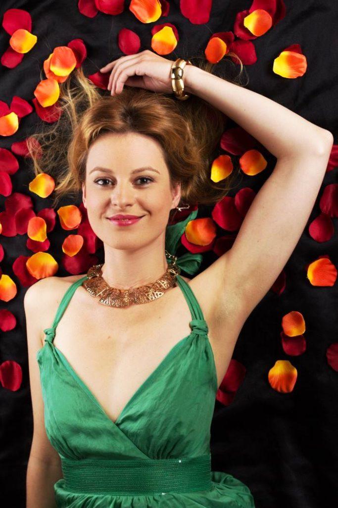 Das jadegrüne Hallhuber Kleid wird präsentiert in einem kleinen Meer aus Rosenblättern.