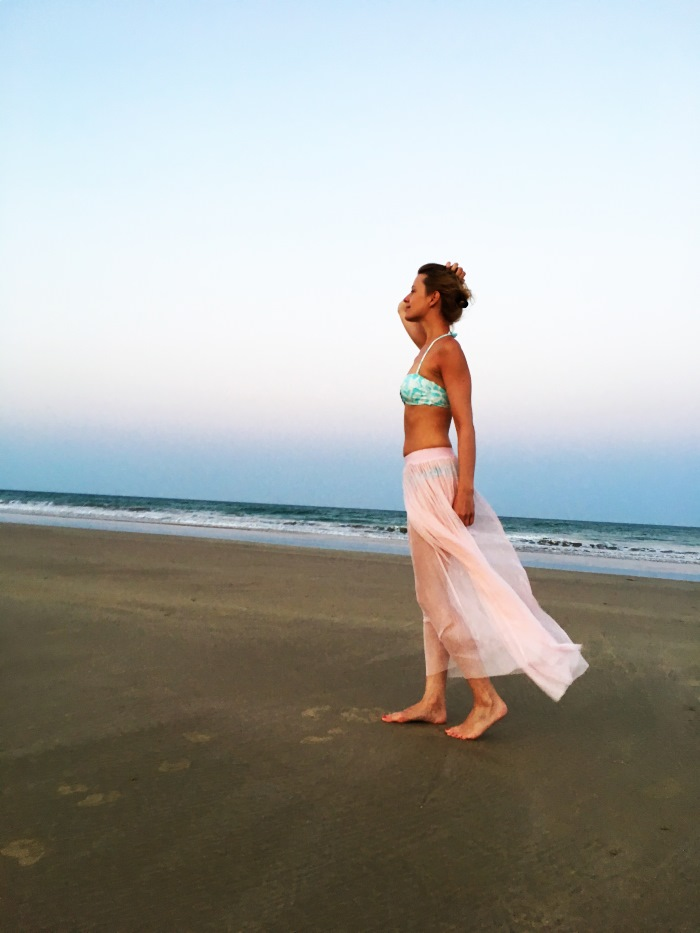 Am Strand in Spanien. Im Hintergrund ein Sonnenaufgang. Ich trage einen Bikini und einen leichten Rock aus Tüll.